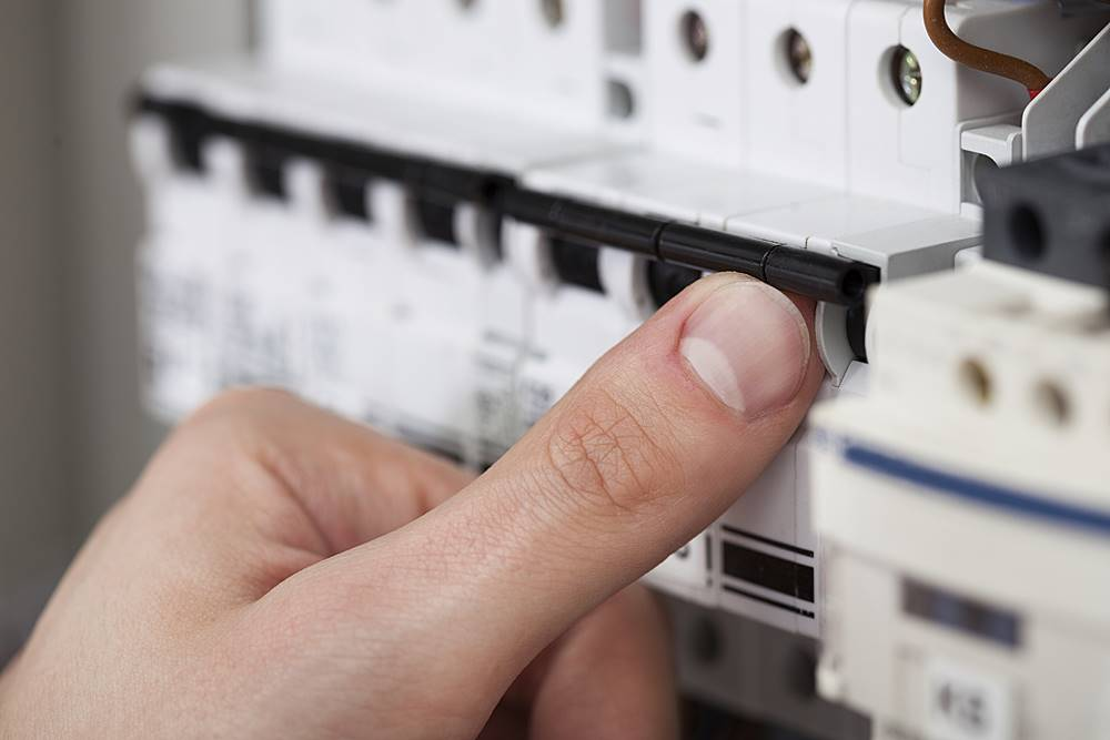 Technician Turning On Switch In Fusebox